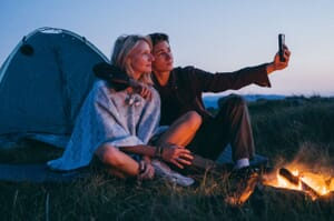Young couple camping taking selfie