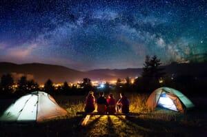 Family camping under night sky stars
