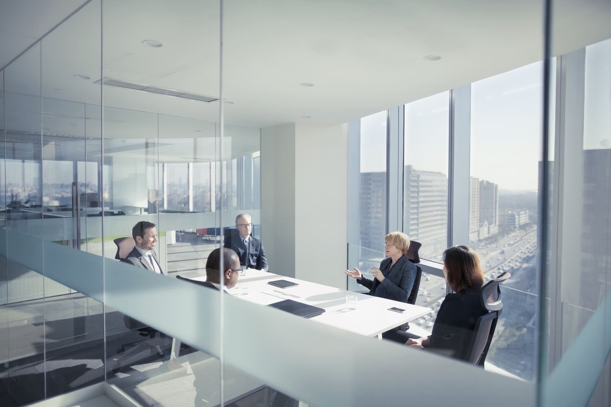 Meeting in a modern glass wall boardroom