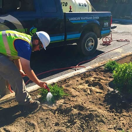 North Point Outdoors employee watering a new commercial landscaping bed