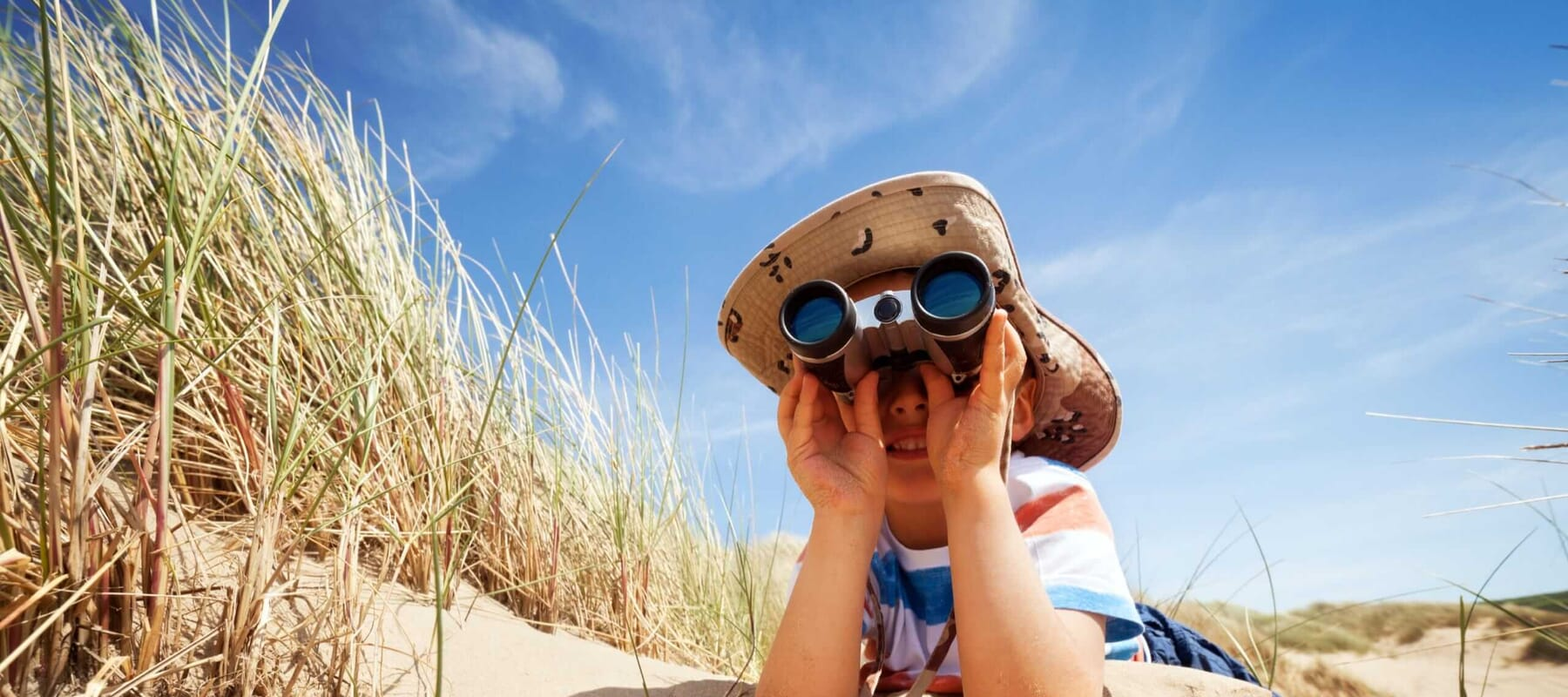 Boy at the beach searching with binoculars