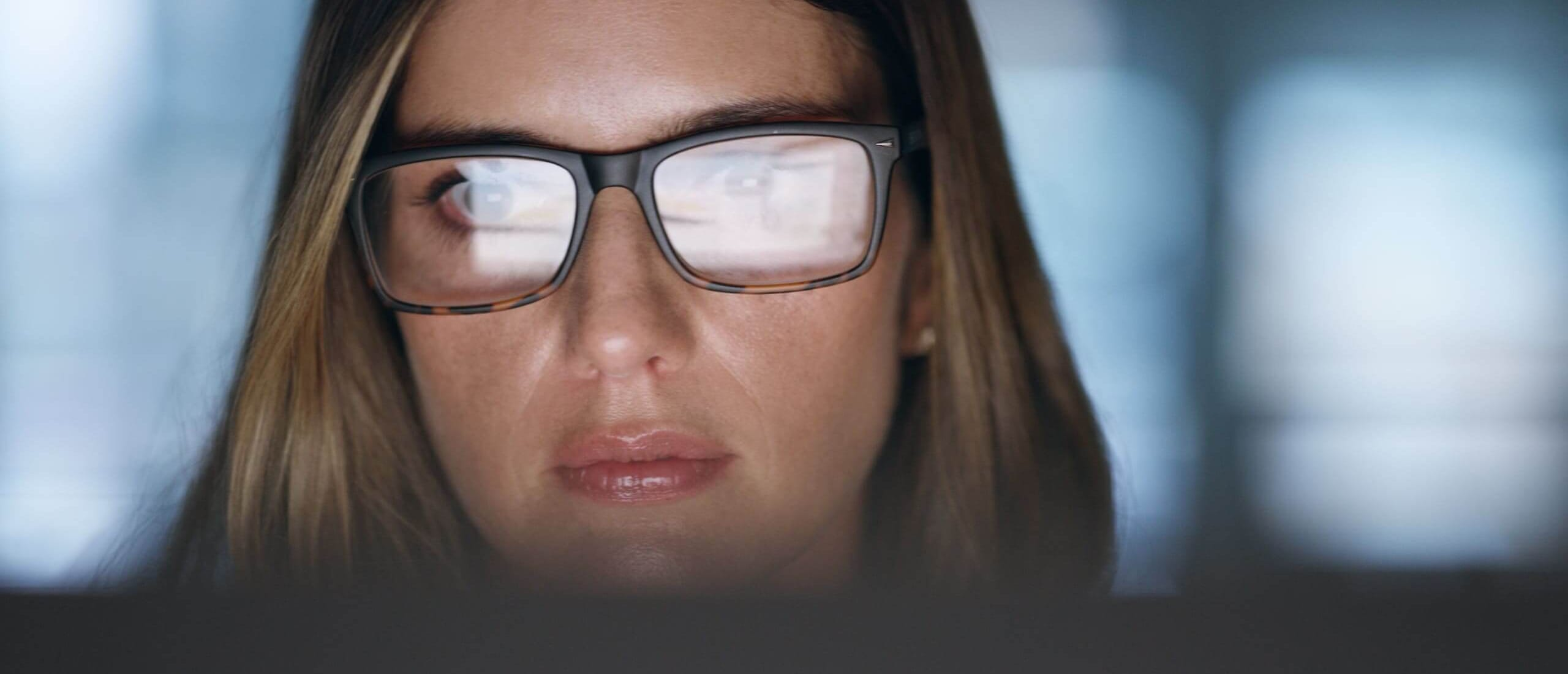 Woman with glasses reflecting computer screen