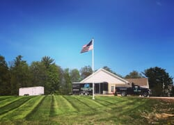Landscaping truck parked on a hill next to American flag on flagpole