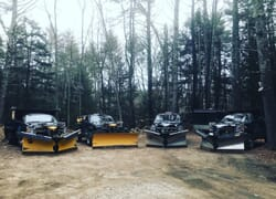 A line of residential NH snow plow trucks