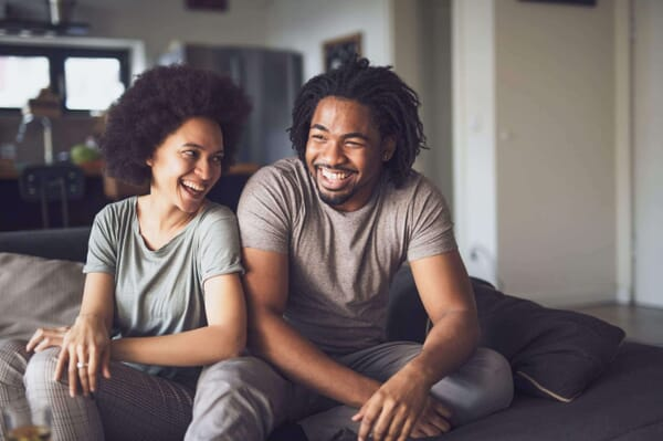 Smiling young black couple sitting on couch